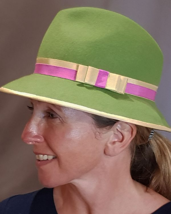 Green felt hat with cream and pink trim worn by model
